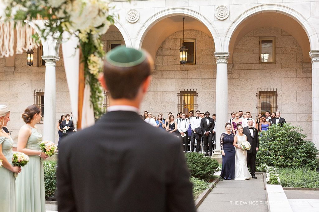The bride approaches her groom during their jewish ceremony at the Boston Public Library.