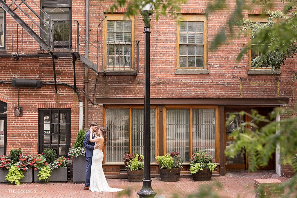 A bride and groom meet for a first look in McKinley Square by Boston's historic Custom House Tower and Marriott.