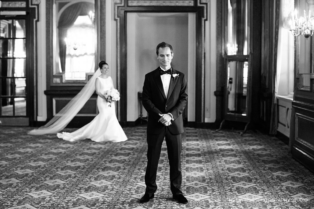 A bride and groom first look moment in the St James Room at the Fairmont Copley Boston, across the street from their Boston Public Library wedding venue.