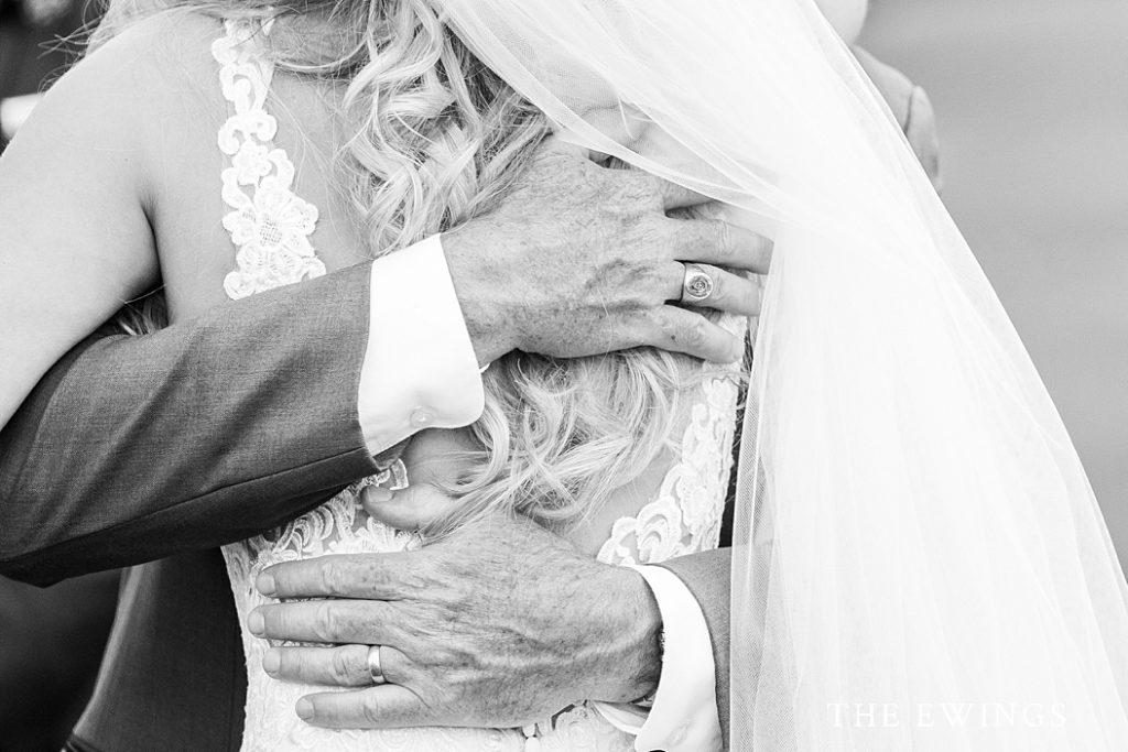 A bride's dad's love is expressed through his warm embrace during her wedding ceremony.