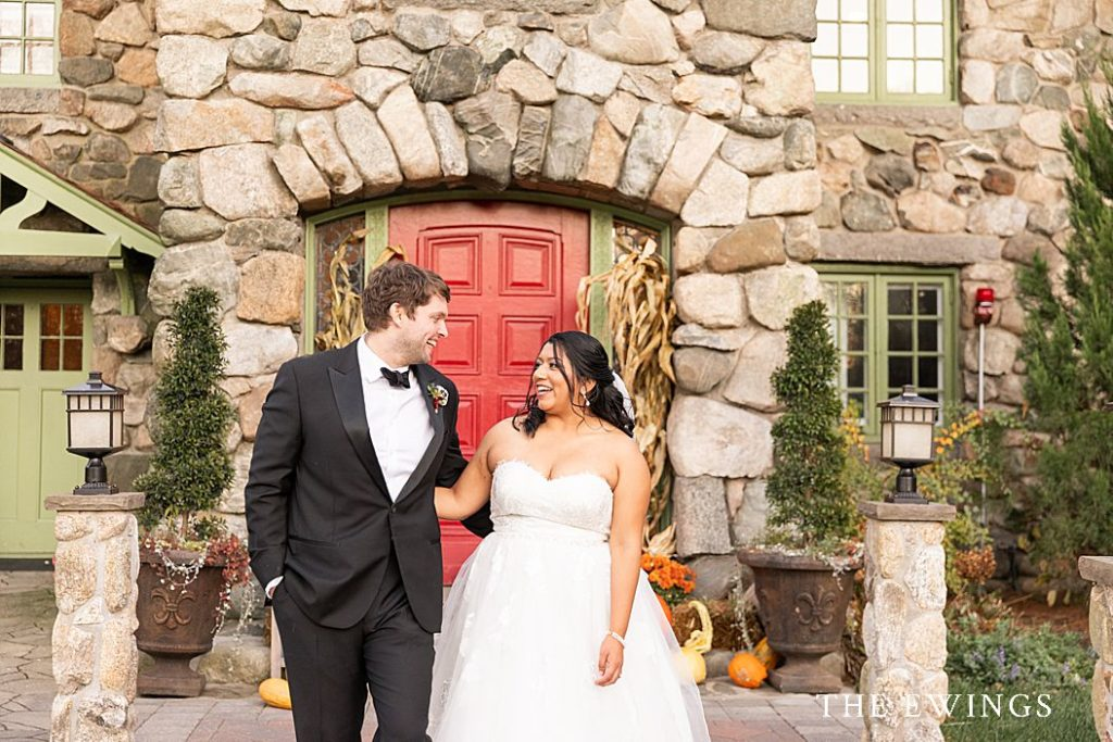This is a wedding at Willowdale Estate, with a bride and groom laughing in front of the mansion.