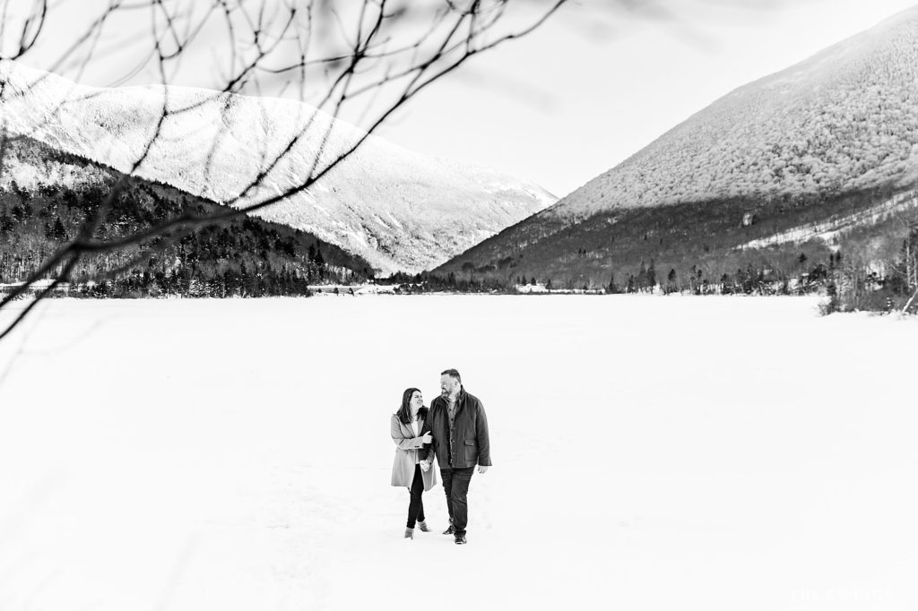 A couple walks across frozen Echo Lake during their Franconia NH engagement session.