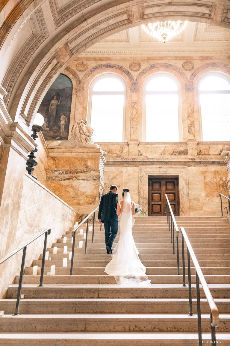A picture of a bride and groom walking up the stairs on their wedding day at Boston Public Library. Their wedding ceremony was in the BPL courtyard.