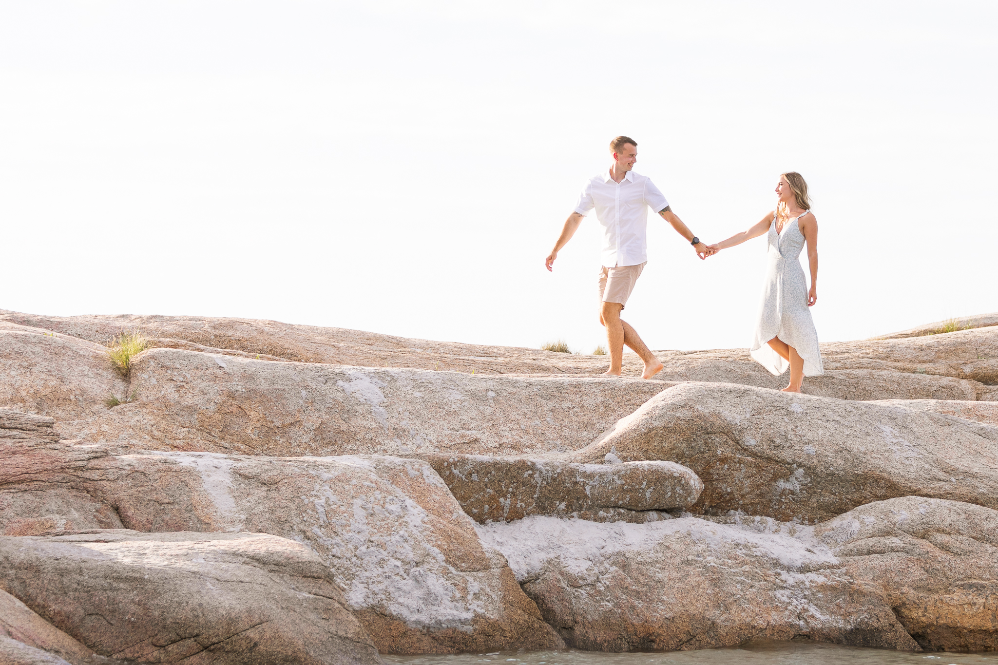 A man and woman walking the rocks at Wingaersheek Beach during their engagement session.