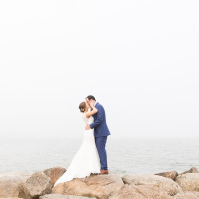 This is a portrait of a bride and groom at Popponesset Beach in Falmouth by the best Cape Cod wedding photographers, The Ewings.